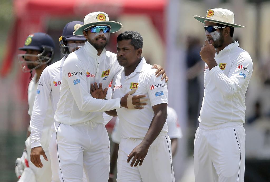 Sri Lanka's Rangana Herath, center without cap, celebrates with teammates the dismissal of India's Ravichandran Ashwin during their second cricket tes...