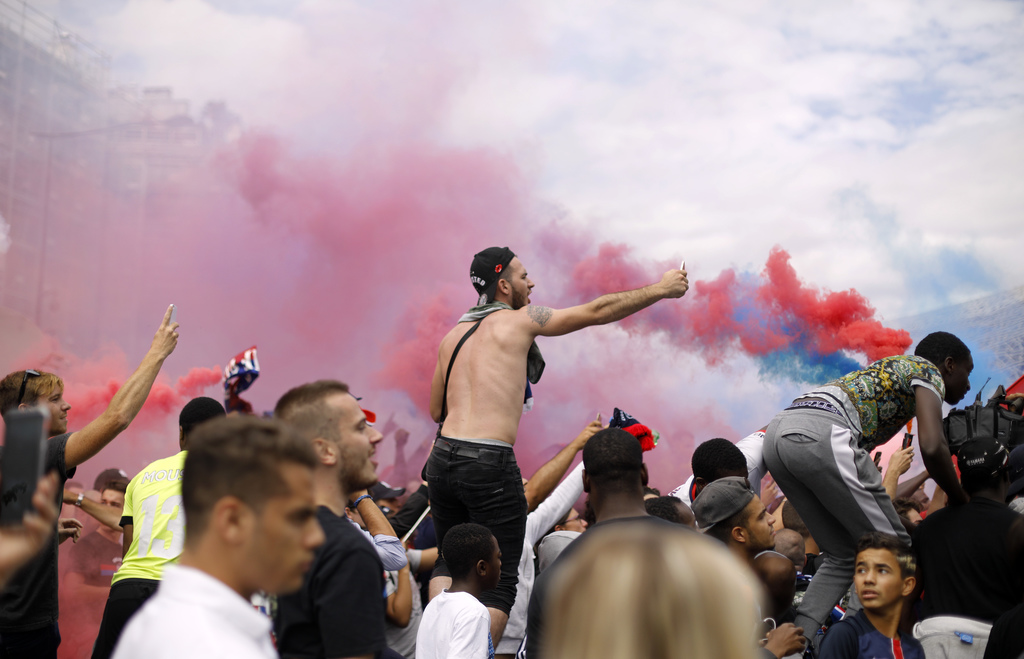 PSG fans react after the arrival of Brazilian soccer star Neymar who was attending a press conference at the Parc des Princes in Paris Friday, Aug. 4,...