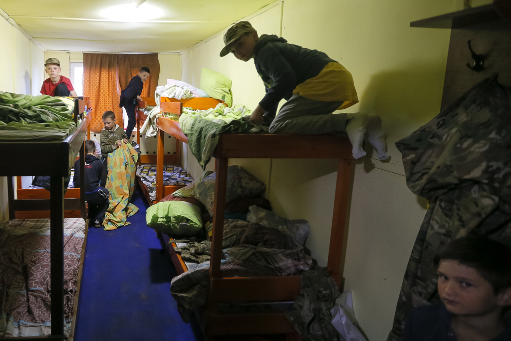 In this photo taken on Friday, July 14, 2017, students at a paramilitary camp for children train to make their beds on time outside Kiev, Ukraine. As ...