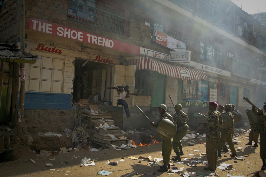 In this photo taken Saturday, Dec. 29, 2007, a looter runs straight into a group of riot policemen, during post-election violence in the Mathare slum ...