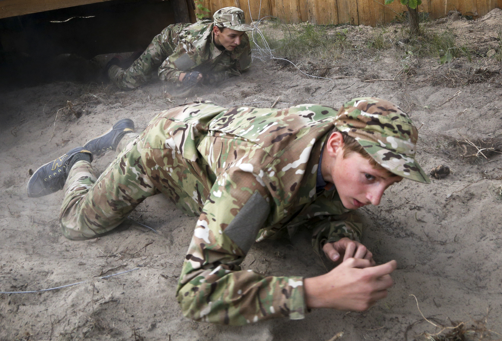 In this photo taken on Saturday, July 8, 2017, students at a paramilitary camp for children work their way through an obstacle course outside Kiev, Uk...