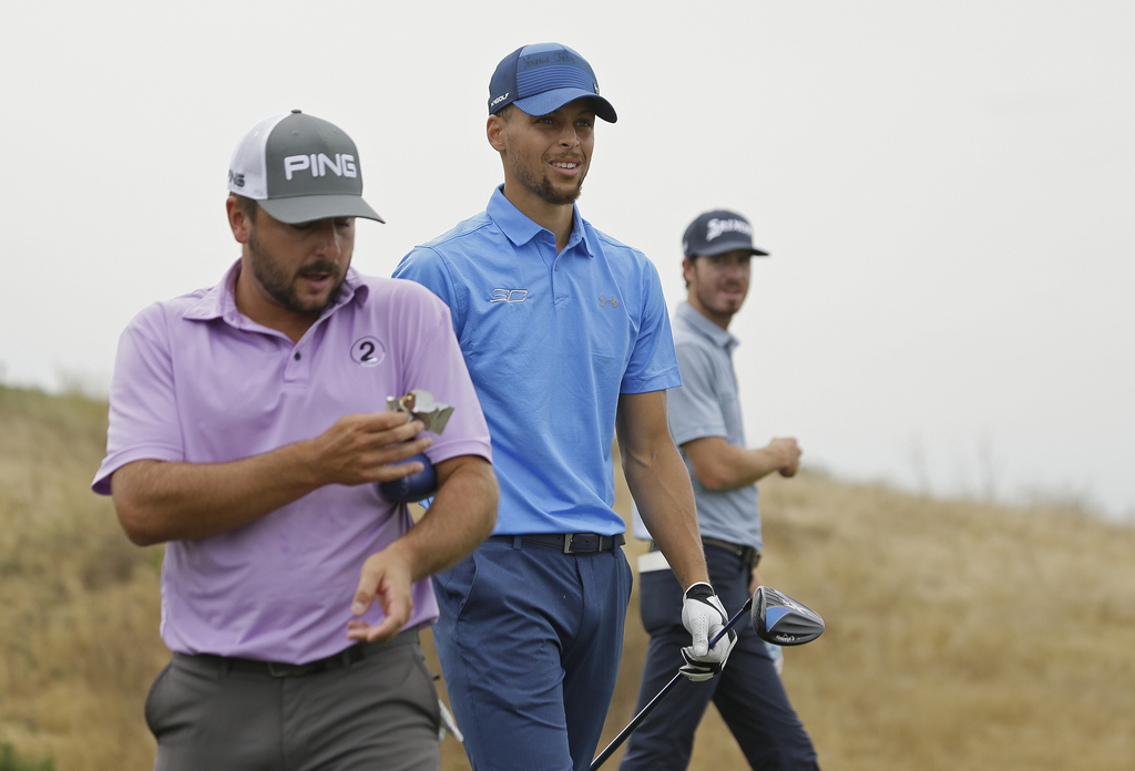 Golden State Warriors NBA basketball player Stephen Curry, center, walks with playing partners Stephen Jaeger, left, and Sam Ryder, right, down the 17...