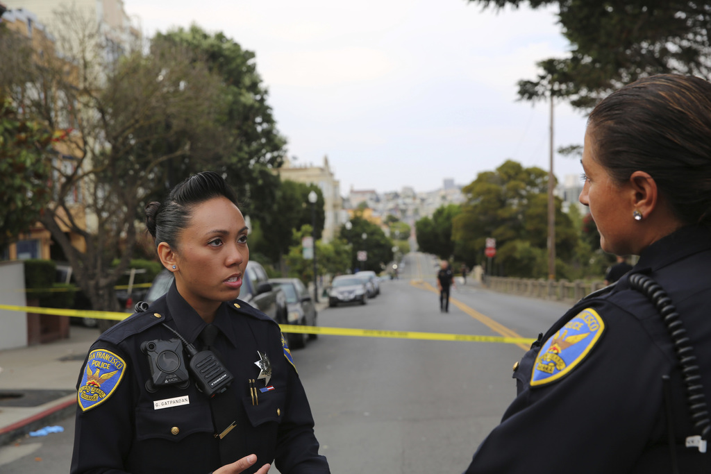 San Francisco Police Officer Grace Gatpandan speaks with another officer as they respond to reports of a shooting at Dolores Park in San Francisco on ...