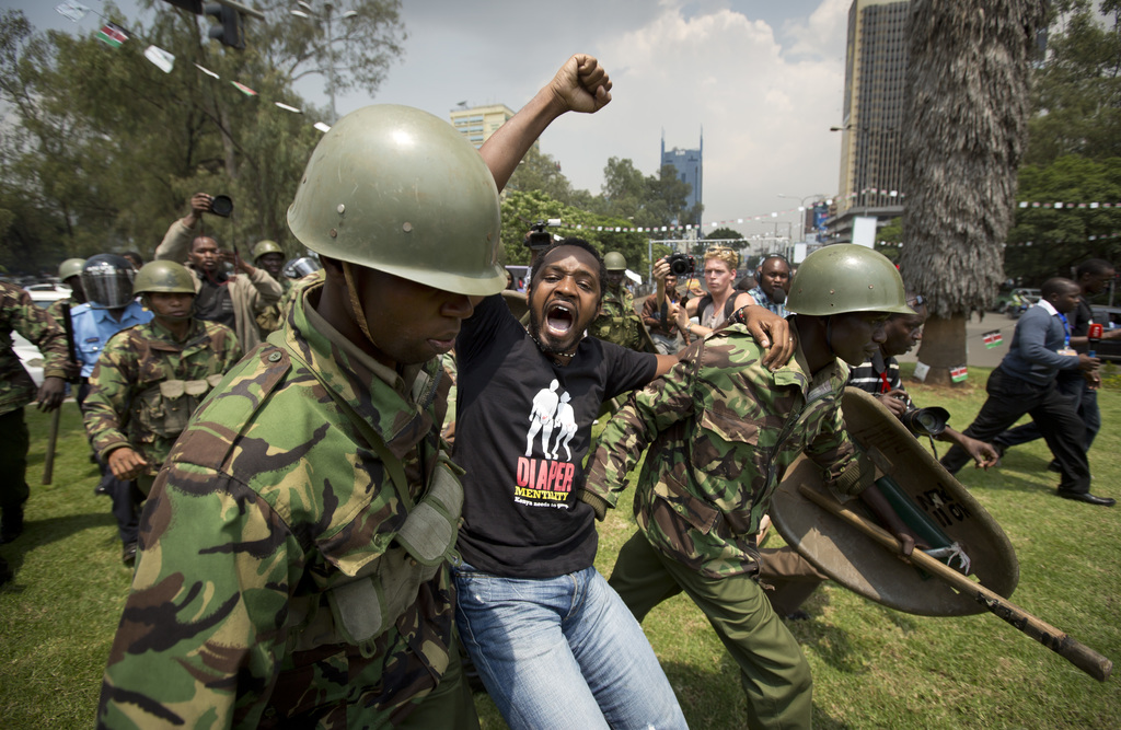FILE - In this Thursday, Feb. 13, 2014 file photo, activist and protest leader Boniface Mwangi raises his fist in the air as he is dragged away to be ...