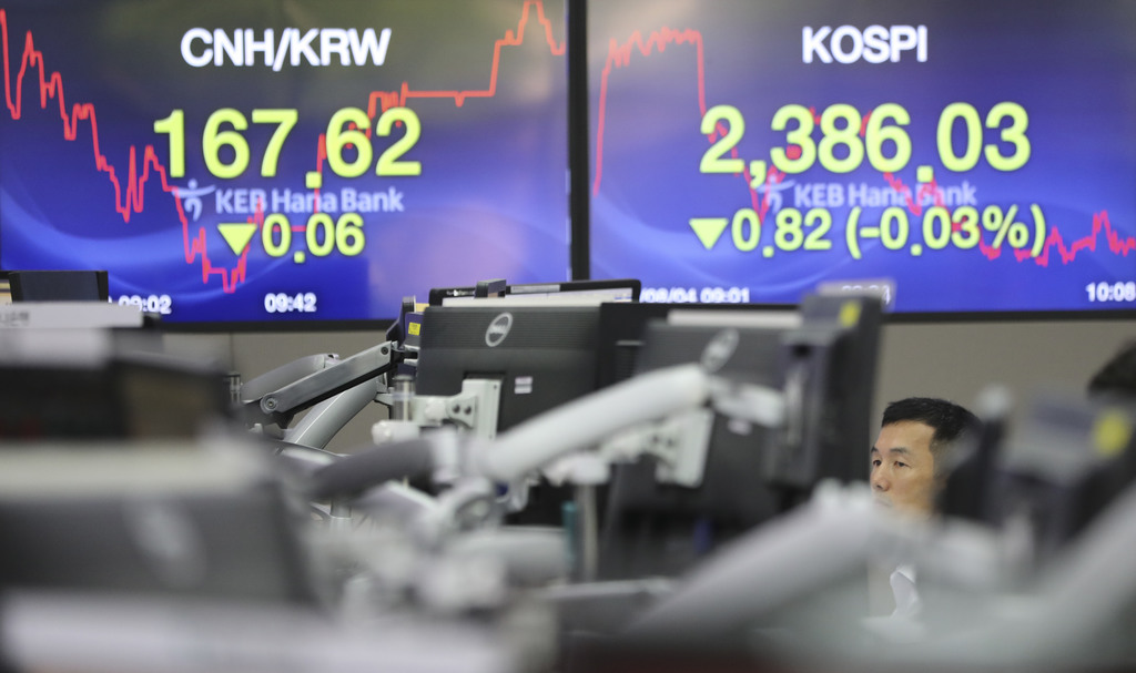 A currency trader watches monitors near the screens showing the Korea Composite Stock Price Index (KOSPI), right, and the foreign exchange rates at th...