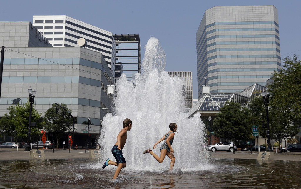 Langstrom Kalstrom, left, and Violet Dashney run through the Salmon Street Springs fountain in Portland, Ore., Thursday, Aug. 3, 2017. The National We...