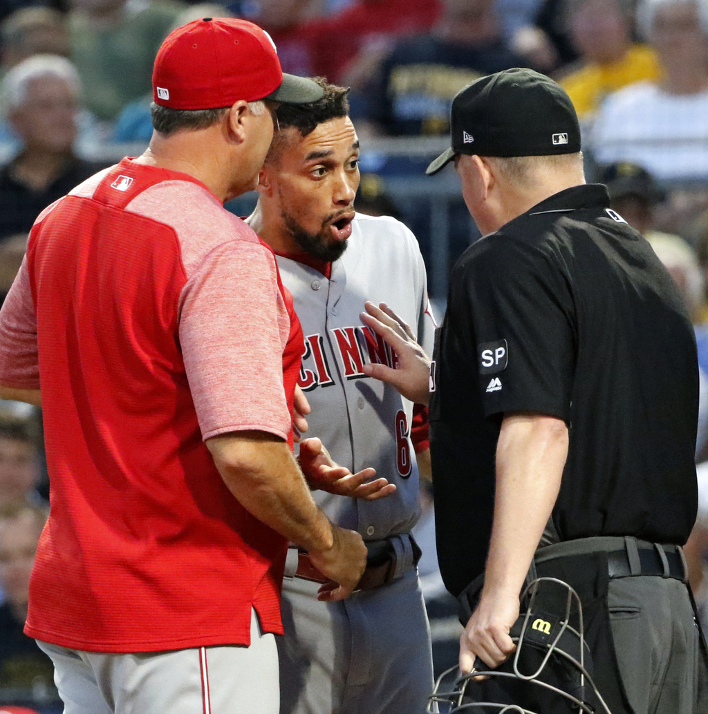 After being ejected for arguing balls and strikes, Cincinnati Reds' Billy Hamilton, center, has his say with umpire Todd Tichenor, right, as manager B...