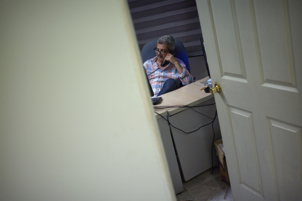 In this June 30, 2017 photo, Ismail Bojorquez, 60, co-founder and director of Riodoce, speaks on the phone as he prepares the weekly edition at his of...