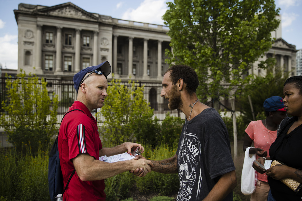 In this Monday, July 24, 2017 photo, Adam Bruckner with Philly Restart, left, helps Steven Kemp, who is addicted to heroin and is homeless to obtain a...