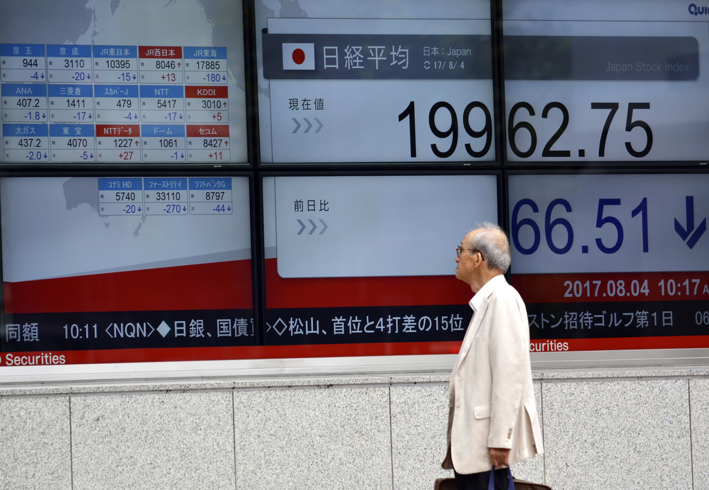 A man stops to look at an electronic stock board outside a securities firm in Tokyo, on Friday, Aug. 4, 2017. Most Asian stock markets were mixed Frid...