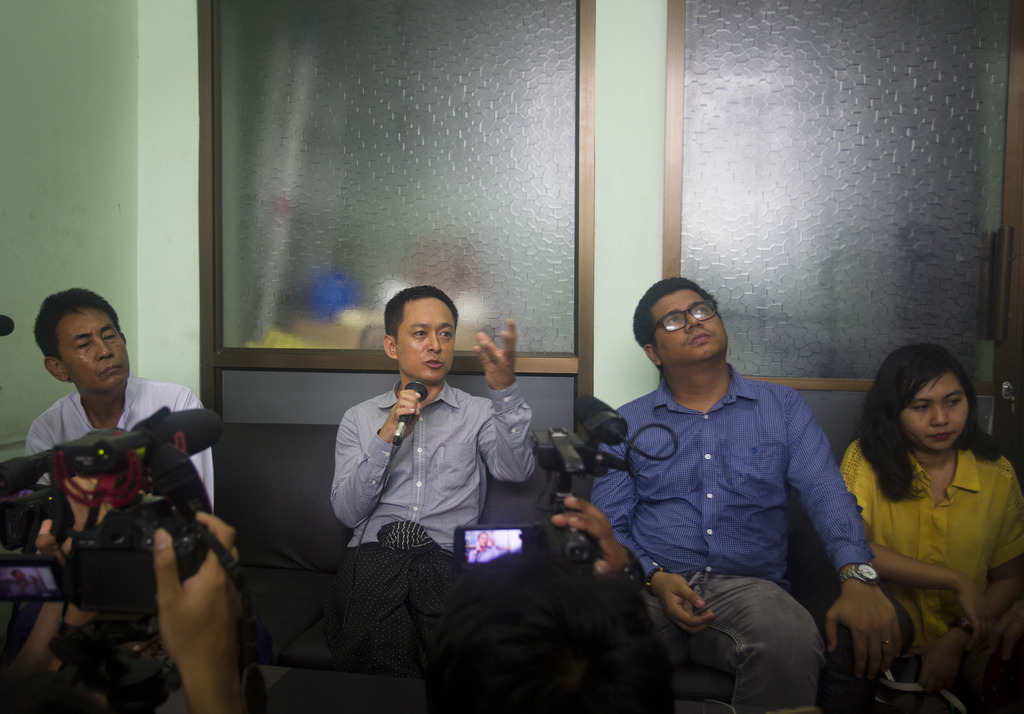 Kyaw Min Swe, second left, chief editor of The Voice Daily newspaper, talks to media during a press briefing along withhis lawyer Khin Maung Myint, le...