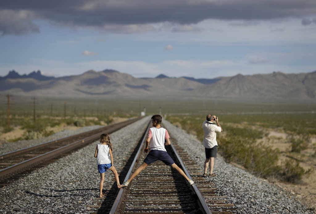 A family walks along train tracks, Thursday, Aug. 3, 2017, in Nipton, Calif. One of the nation's largest cannabis companies announced it has bought th...