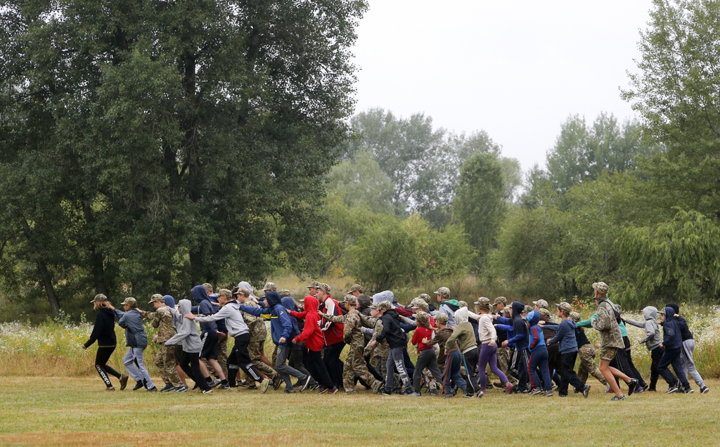 In this photo taken on Friday, July 14, 2017, students at a paramilitary camp for children take part in orientation exercises outside Kiev, Ukraine. A...