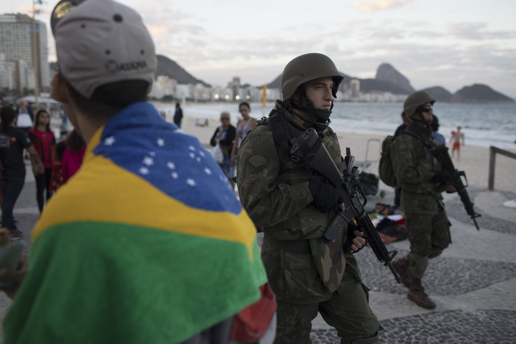 In this Sunday, July 30, 2017 photo, soldiers patrol Copacabana beach in Rio de Janeiro, Brazil. Thousands of soldiers began patrolling Rio de Janeiro...