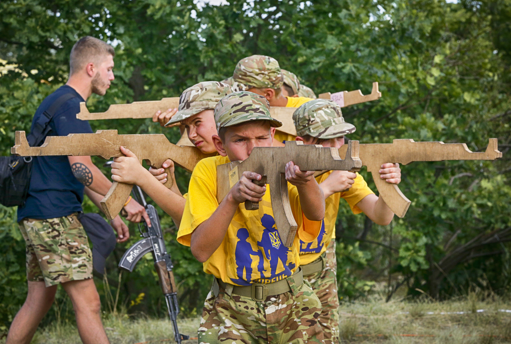In this photo taken on Saturday, July 8, 2017, students at a paramilitary camp for children holding wooden mock-rifles with the trainer, left, with a ...
