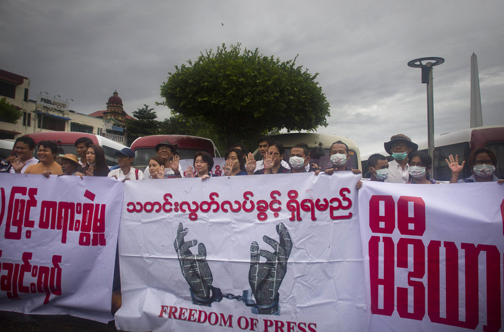 In this photo taken June 30, 2017, journalists and activists standing behind banners as they rally for press freedom in Yangon, Myanmar. Myanmar's cou...