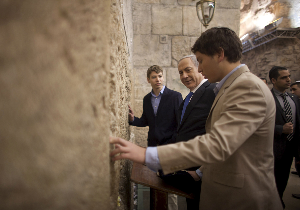 FILE - In this Jan. 22, 2013 file photo, Israeli Prime Minister Benjamin Netanyahu, center, prays with his sons Yair, background, and Avner, right, at...