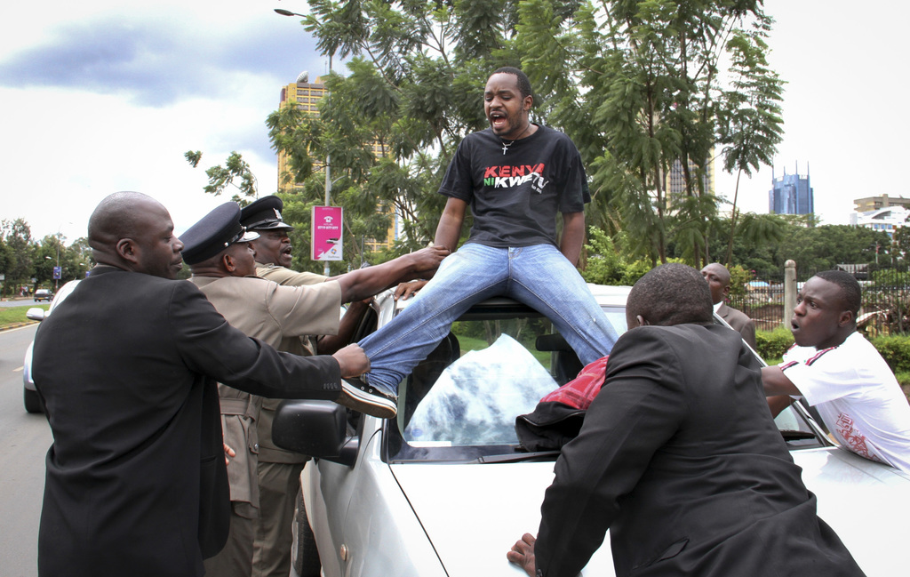 FILE - In this Wednesday, May 1, 2013 file photo, Boniface Mwangi, center, is arrested by security forces while staging a protest during Labor Day cel...