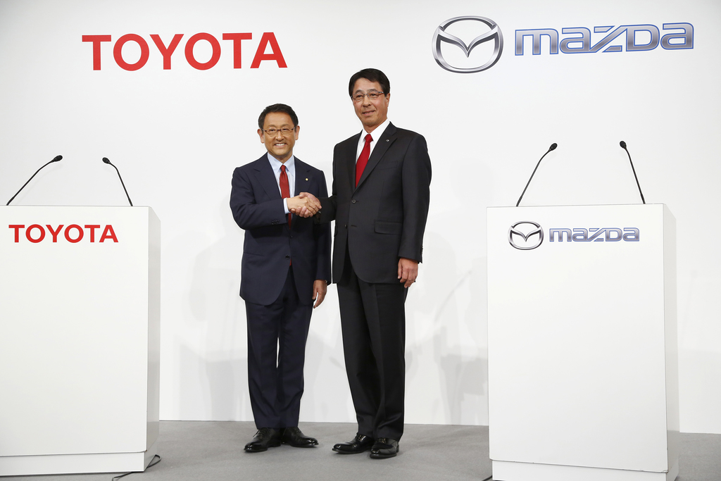 FILE - In this May 13, 2015 file photo, Toyota Motor Corp. President Akio Toyoda, left, and Mazda Motor Corp. President Masamichi Kogai pose for photo...
