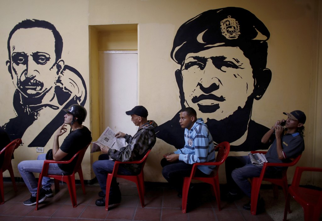 In this Sunday, July 30, 2017 photo, voters wait to cast their ballots next murals of Venezuelan independence hero Ezequiel Zamora, left, and late Ven...