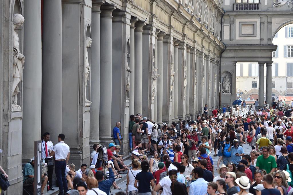 Tourists queueing to enter the Uffizi Gallery in Florence, Italy, Friday, Aug. 4, 2017. An air-conditioning breakdown has caused the Uffizi Galleries ...