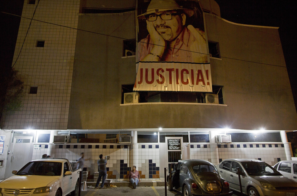"In this July 2, 2017 photo, a banner of slain journalist Javier Valdez and the word in Spanish ""Justice!"" hangs from the Riodoce newspaper building as..."