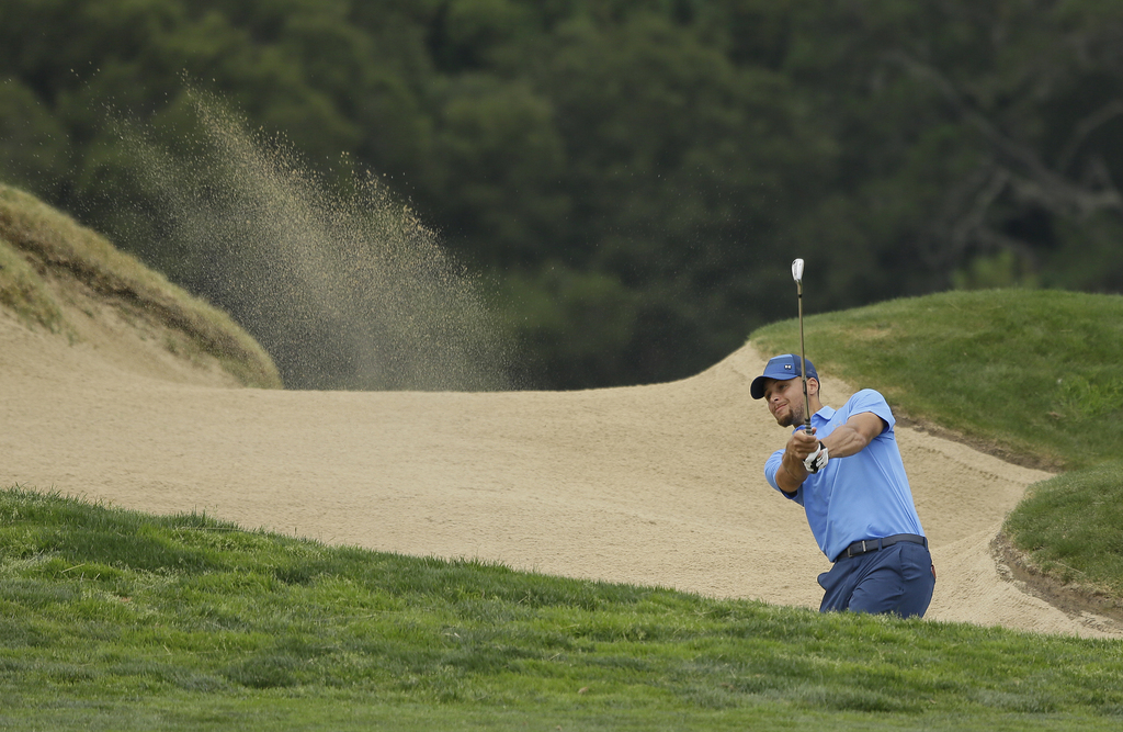 Golden State Warriors NBA basketball player Stephen Curry follows his shot out of a bunker on the 18th fairway during the Web.com Tour's Ellie Mae Cla...