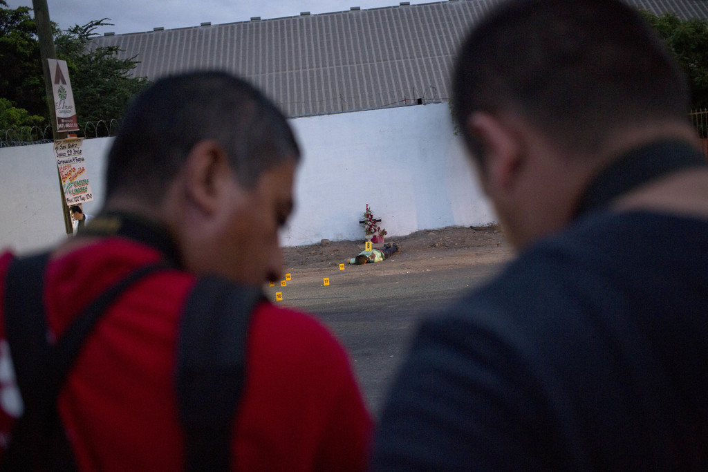 In this June 29, 2017 photo, journalists report from the site where three bullet ridden bodies were found in Navolato, on the outskirts of Culiacan, S...