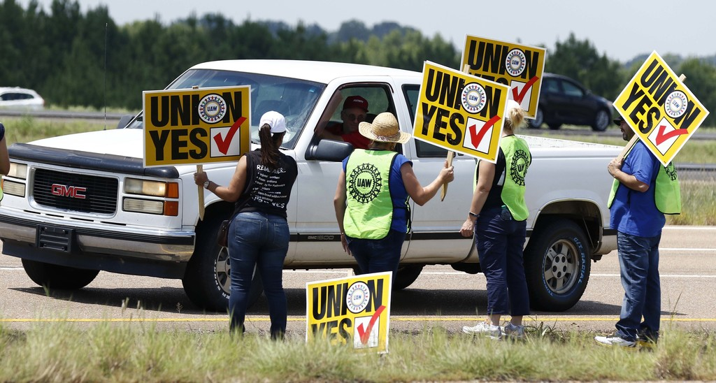 United Auto Workers members and their volunteers stand out alongside the access road to the Nissan vehicle assembly plant in Canton, Miss., and greet ...