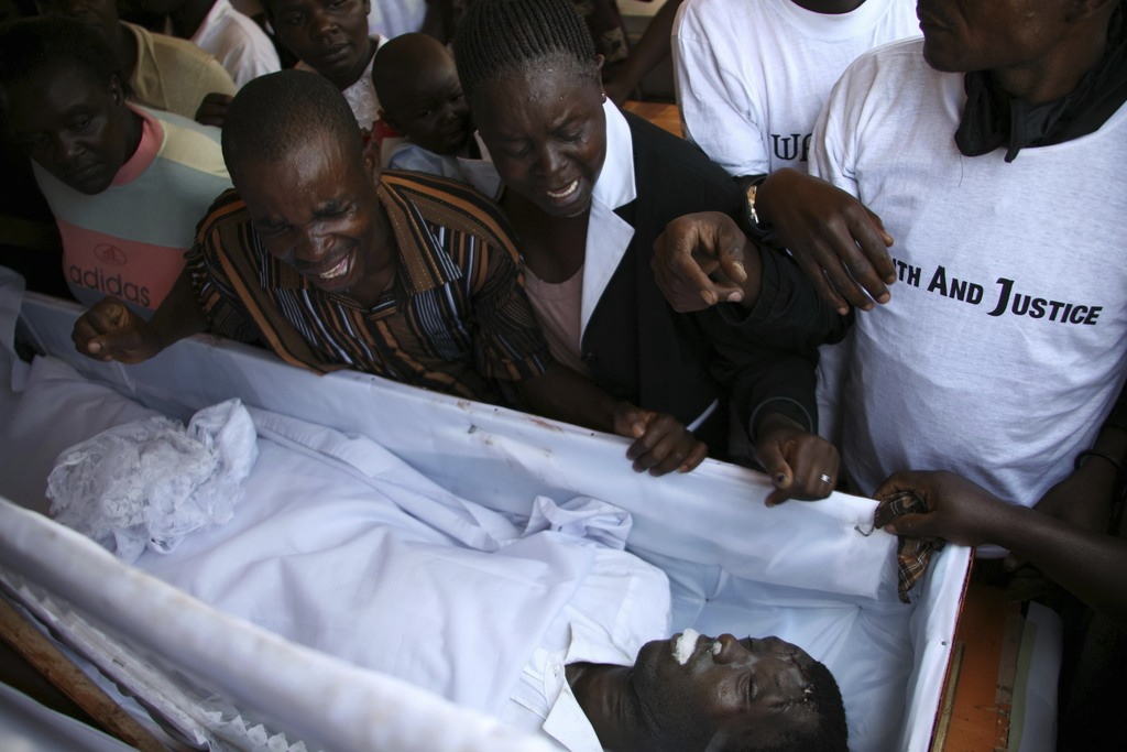 In this photo taken Wednesday, Jan. 23, 2008, relatives weep during a mass for a victim of the post-election violence in Nairobi, Kenya. Appalled by g...