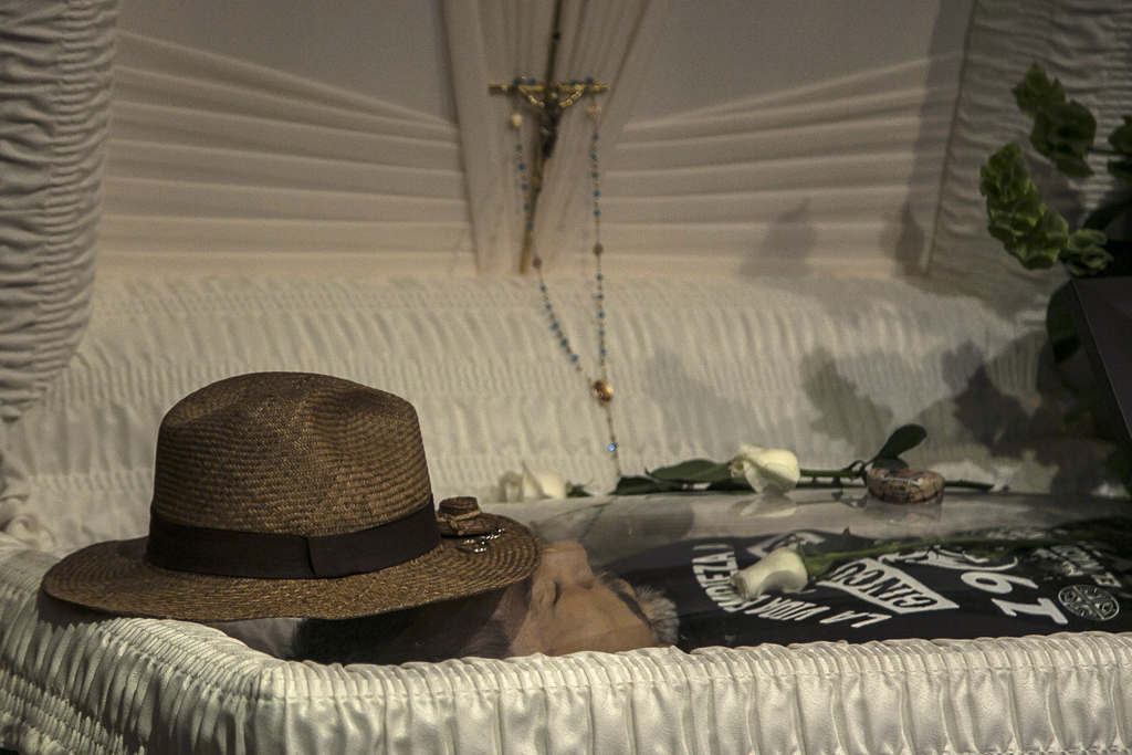 FILE - In this May 16, 2017 file photo, the hat of slain journalist Javier Valdez lays on his forehead inside a funeral home before his wake begins in...