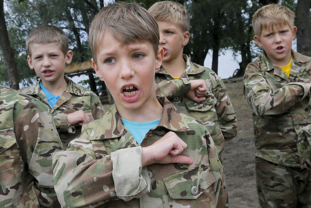 In this photo taken on Friday, July 14, 2017, students at a paramilitary camp for children sing the Ukrainian national anthem before the start of exer...