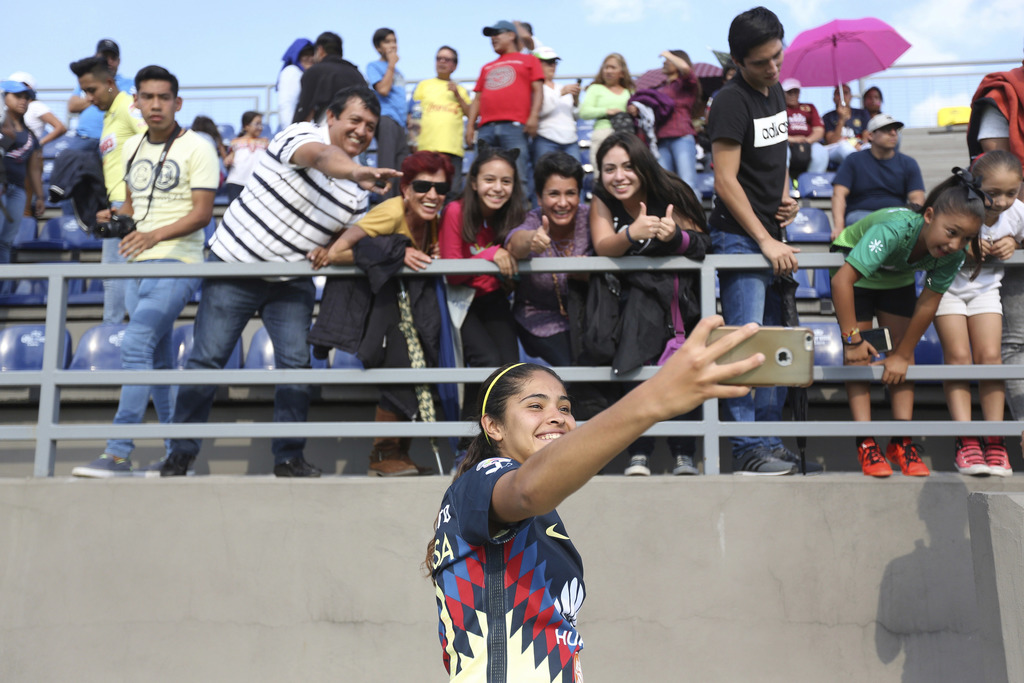 In this July 29, 2017 photo, America's forward Daniela Espinosa, takes a selfie with fans after the inaugural game of Mexico's first women's soccer le...