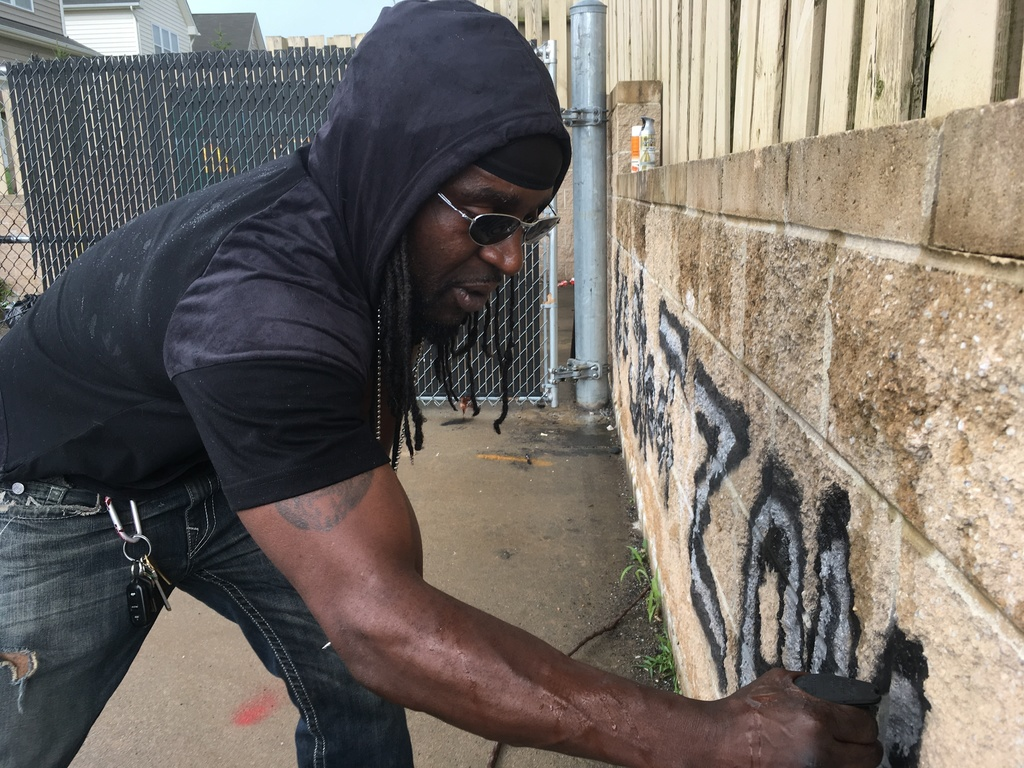 """In this Wednesday, Aug. 2, 2017, photo Tyree Colion spray paints the words """"No Shoot Zone"""" on a brick wall behind a convenience store, in a spot near ..."""
