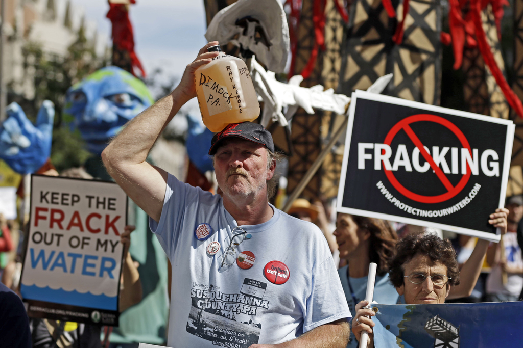 FILE – In this Sept. 20, 2012 file photo, Ray Kemble, of Dimock, Pa., holds a jug of his well water on his head while marching with demonstrators agai...