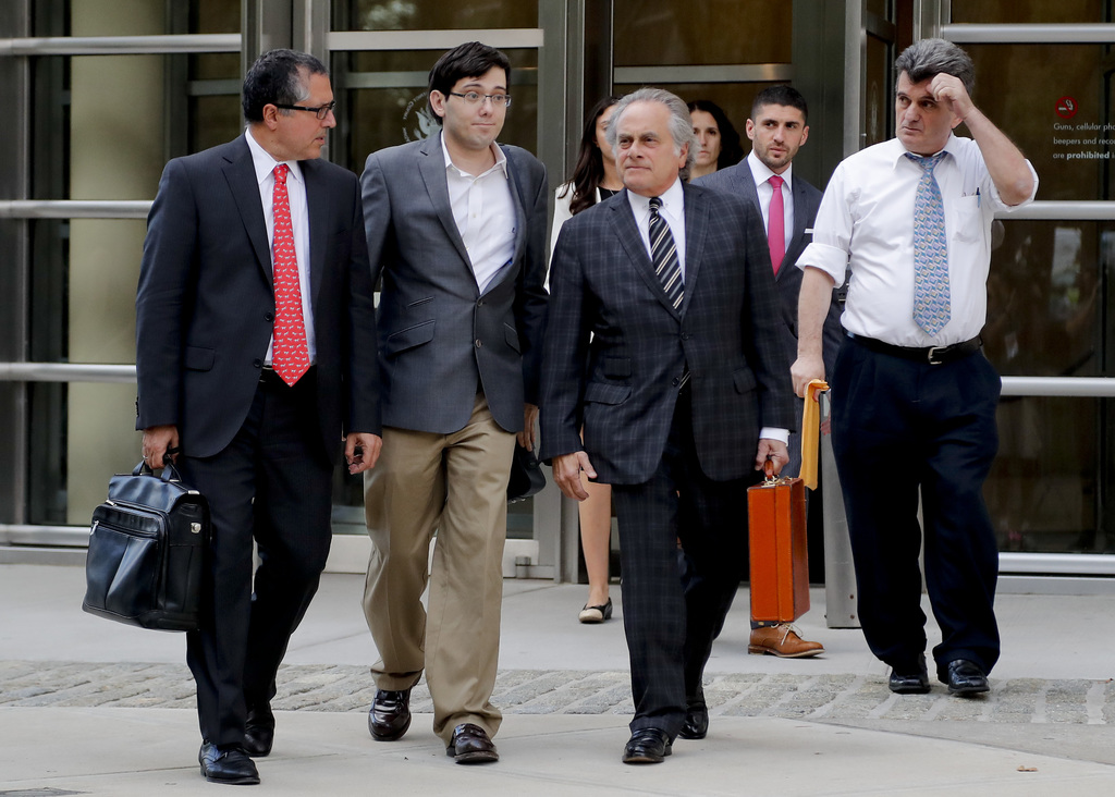 Former pharmaceutical company CEO Martin Shkreli, second from left, walks out of federal court with his legal team Thursday, Aug. 3, 2017, in New York...