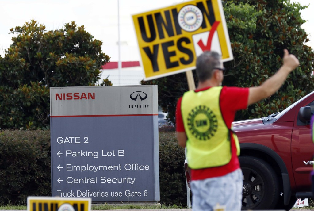 A United Auto Workers sign-bearing member stands outside an employee vehicle entrance at the Nissan vehicle assembly plant in Canton, Miss., and greet...