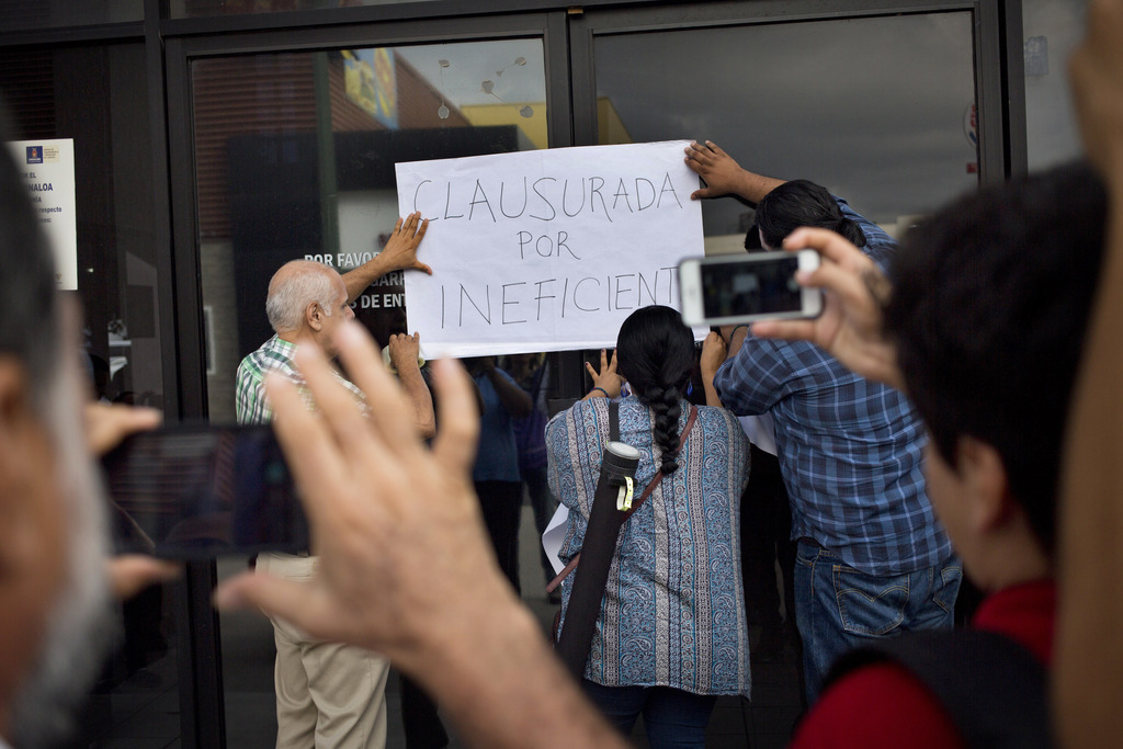 """In this June 28, 2017 photo, journalists place a sign that reads in Spanish """"closed for being inefficient"""" during a demonstration at the Sinaloa state..."""