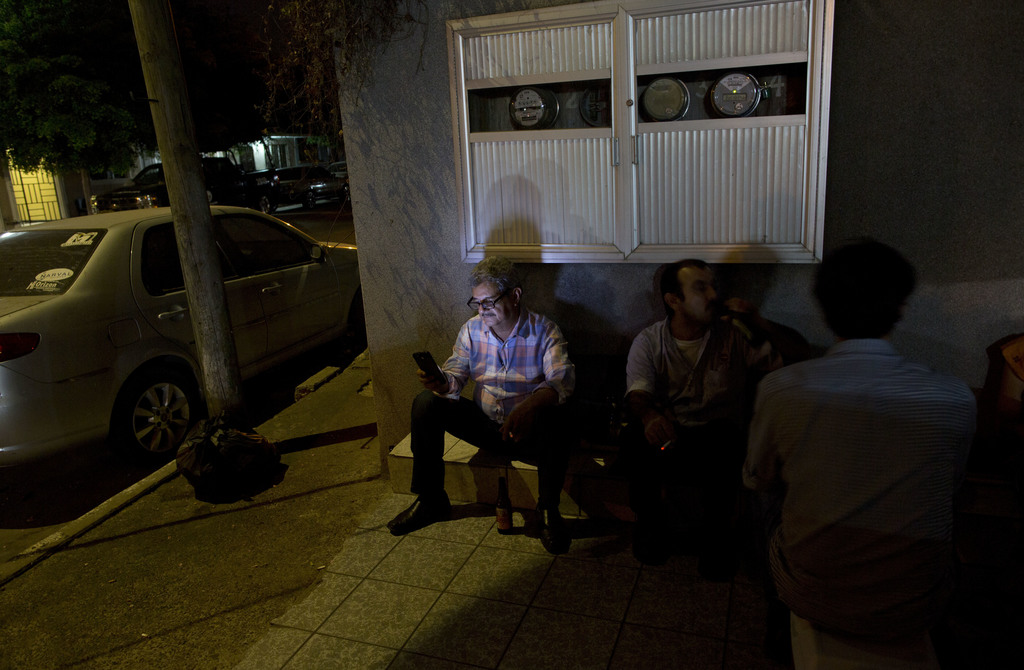 In this July 1, 2017 photo, Ismail Bojorquez, 60, a co-founder and director of Riodoce, works on his cellphone as he and editors sit on the sidewalk o...