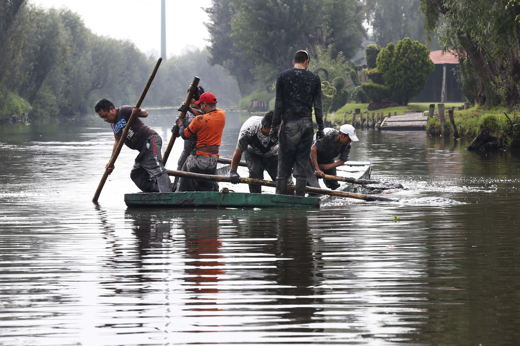 In this July 13, 2017 photo, men remove mud from a shallow canal so tourist boats can move through in Xochimilco, Mexico City. A late July report by t...