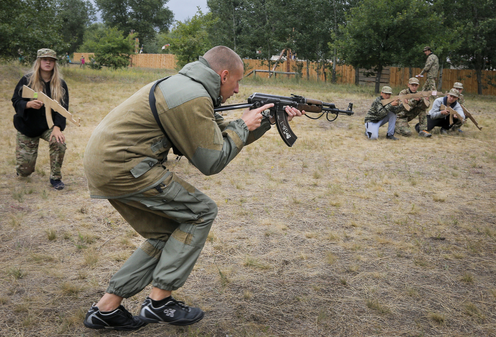 In this photo taken on Friday, July 14, 2017, a trainer at a paramilitary camp for children holds a rifle during exercises outside Kiev, Ukraine. As t...