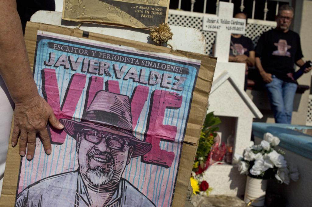 In this July 1, 2017 photo, relatives of slain journalist Javier Valdez, co-founder of Riodoce, stand at a memorial set up at the spot where he was mu...