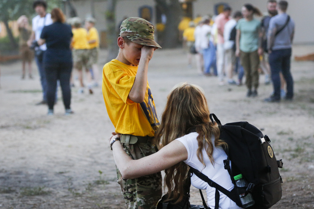 In this photo taken on Saturday, July 8, 2017, a visiting mother consoles her child at a paramilitary camp for children outside Kiev, Ukraine. As the ...