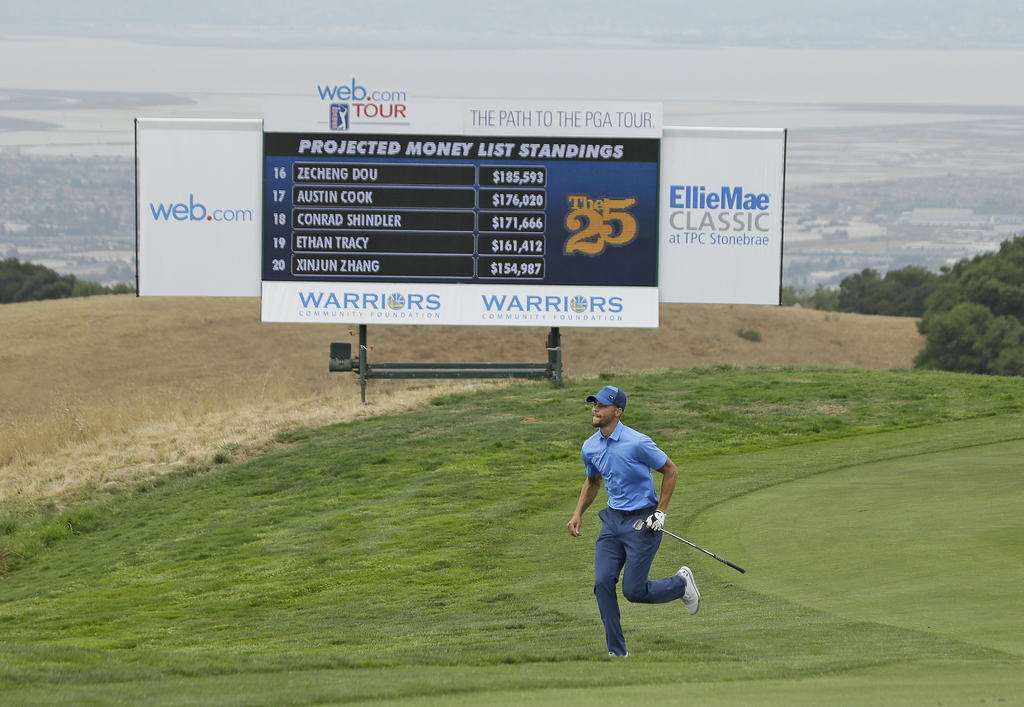 Golden State Warriors NBA basketball player Stephen Curry runs up to take a look at the 18th green before hitting his approach shot during the Web.com...