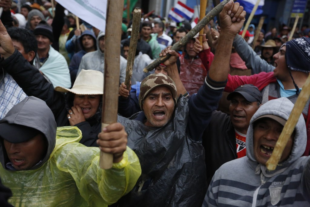 In this Wednesday, Aug. 2, 2017 photo, farmers from northern Paraguay protest in downtown Asuncion, Paraguay. Farmers have been camping out in protest...