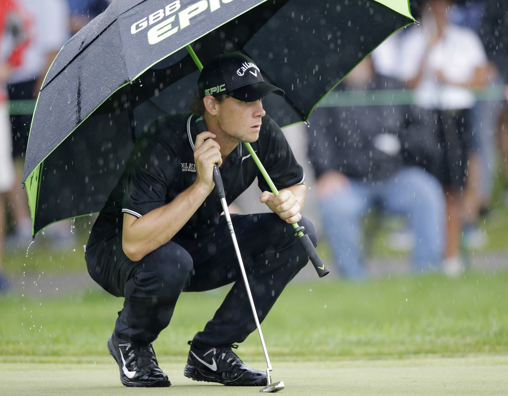 Thomas Pieters, from Belgium, waits to putt on the first green as rain falls during the second round of the Bridgestone Invitational golf tournament a...