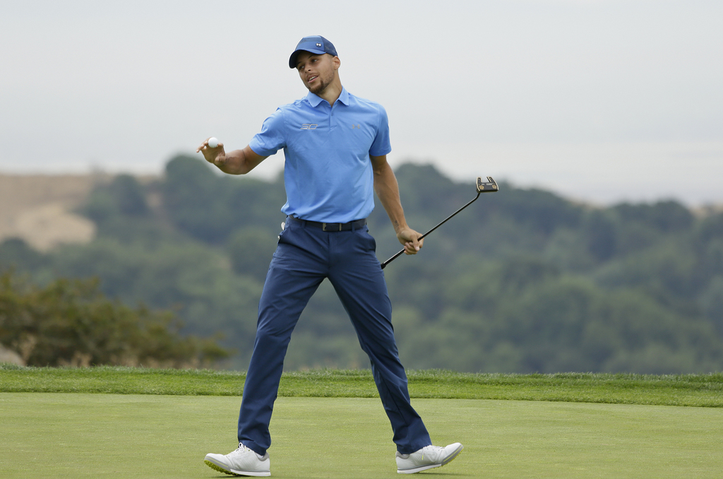 Golden State Warriors NBA basketball player Stephen Curry reacts after saving par on the 18th green during the Web.com Tour's Ellie Mae Classic golf t...