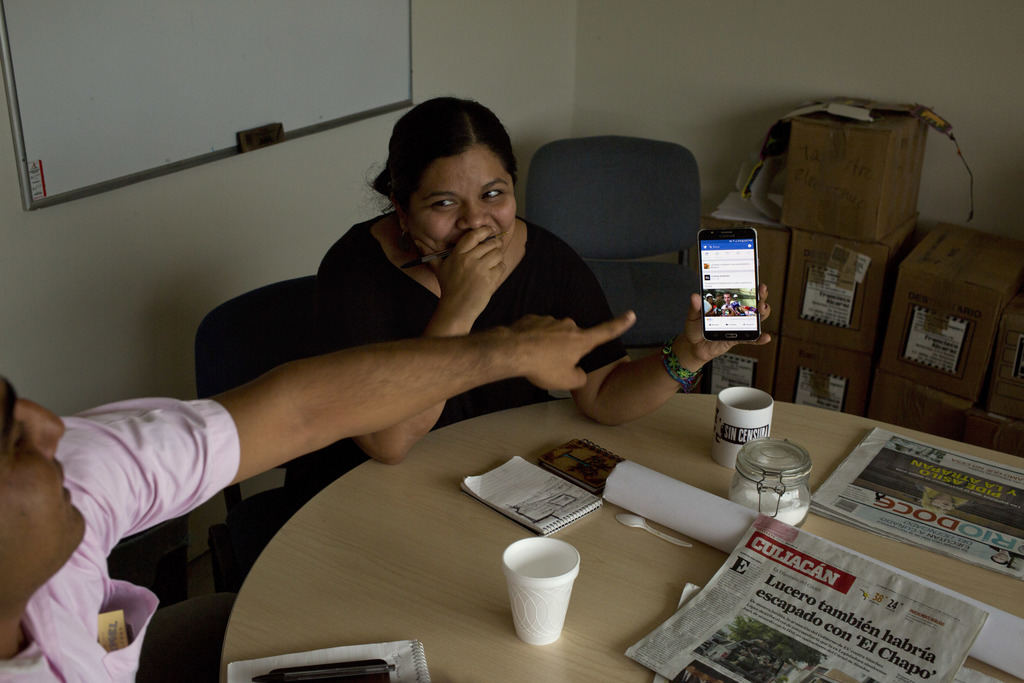 In this June 26 2017 photo, reporter Miriam Ramirez shows a picture on her cellphone to a co-worker during a Riodoce editorial meeting in Culiacan, Si...