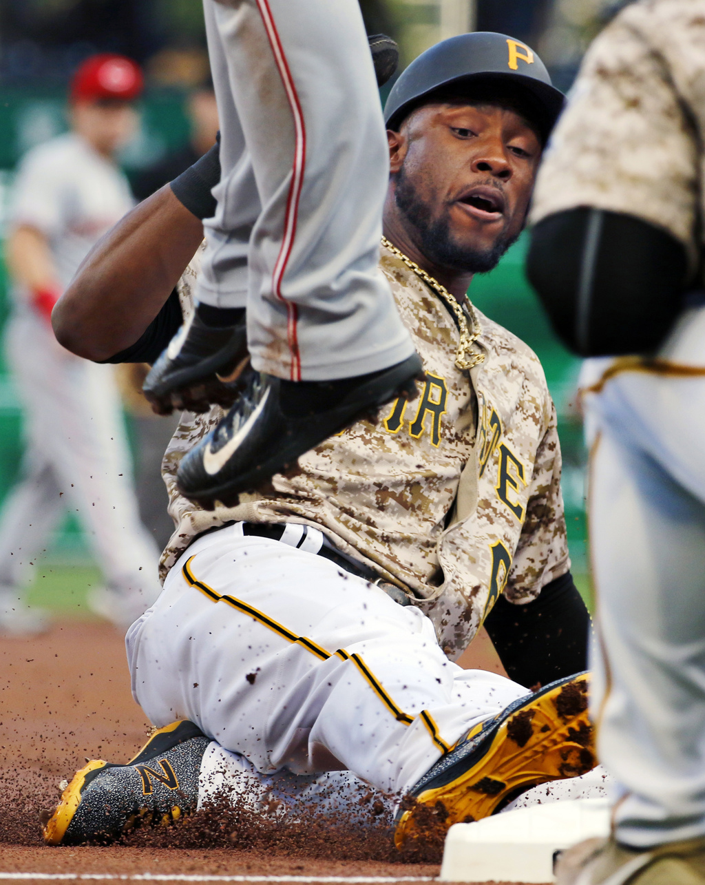 Pittsburgh Pirates' Starling Marte slides safely into third on a single by Adam Frazier, as Cincinnati Reds third baseman Eugenio Suarez leaps for an ...