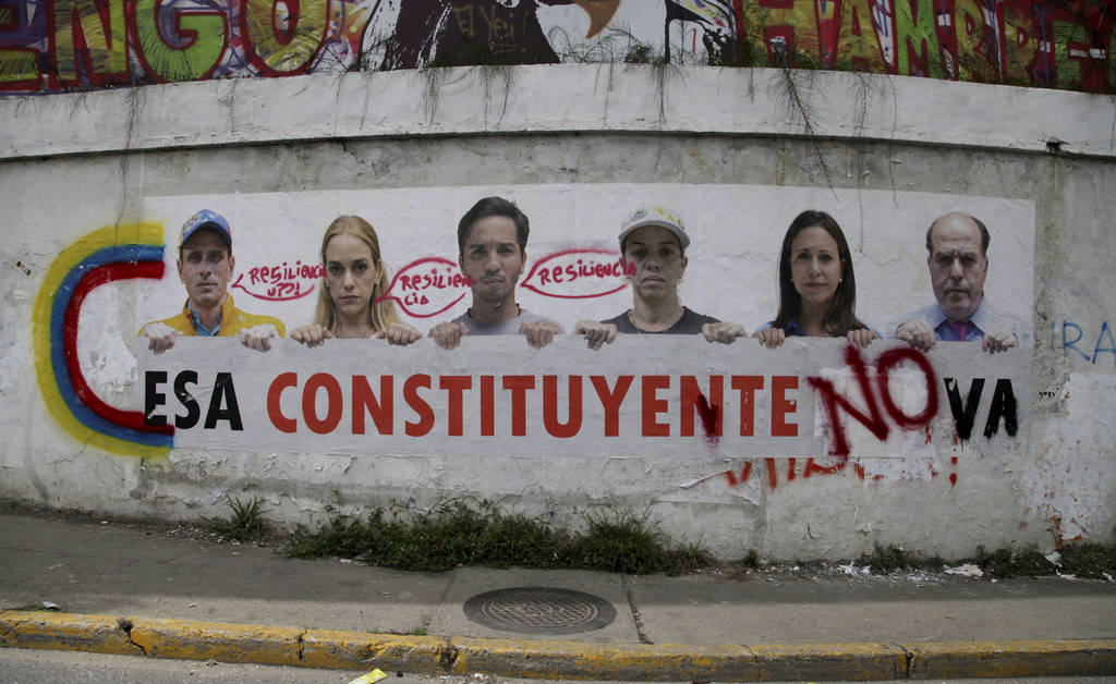 "A poster that shows some of Venezuela's opposition leaders holding a sign with a message that reads in Spanish: ""That constituent assembly will not pa..."